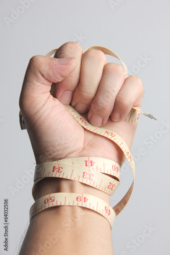 Line measurement tape in hand on gray background