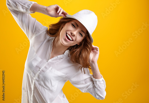 canvas print picture Young Woman with spring hat against yellow background