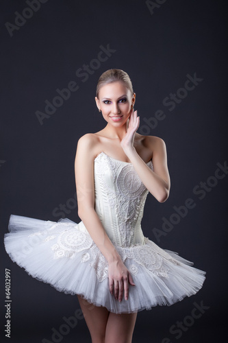 Young charming ballerina posing smiling at camera