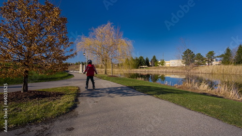 Young Boy Learning To Ride On Rollerblades In The Park.