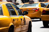 Yellow cab speeds through Times Square in New York, NY, USA. - 64034589
