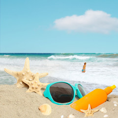 Straw hat, sunglasses, towel and starfish on sand beach.