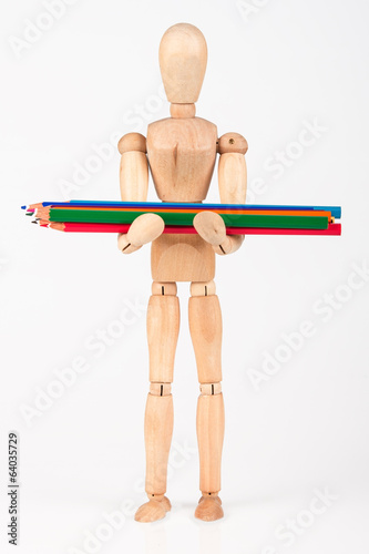 Small wood mannequin standing with bunch of colour pencil isolat