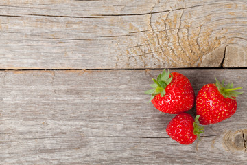 Ripe strawberries over wooden table background