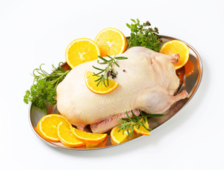 Raw duck with orange slices and herbs on tray