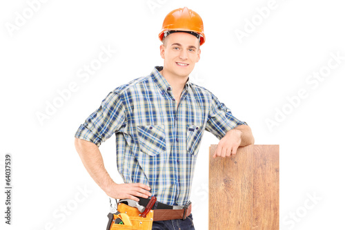 Male carpenter leaning on a plank