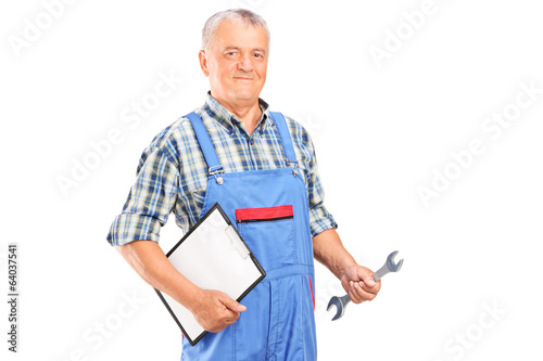 Male mechanic holding a wrench and a clipboard