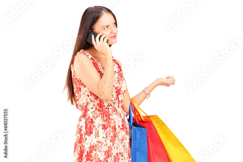 Woman with shopping bags talking on a phone