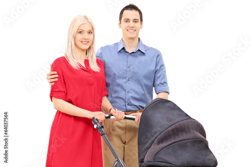 Young parents with a baby stroller posing
