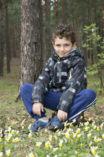 The boy in the woods sitting on a stump.