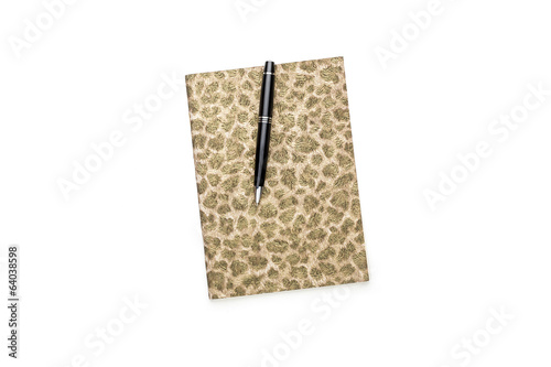closed diary with golden pattern on cover and black ball pen, is