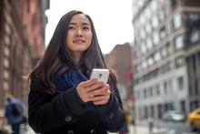 壁紙(ウォールミューラル) - Young Asian woman texting message walking street
