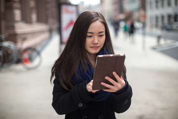 Young Asian woman using tablet pc map gps walking
