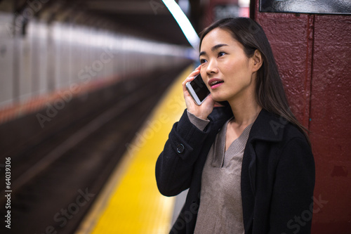 Young Asian woman talking cellphone subway platform
