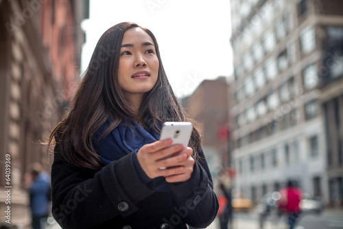 Young Asian woman texting message walking street