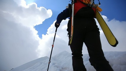 Ski mountaineer walking up along a steep snowy ridge