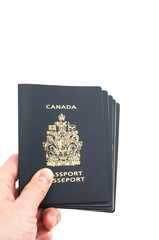 Hand holding five Canadian passports isolated on white backgroun