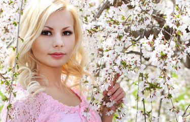 Blonde Girl with Cherry Blossom. Spring Portrait