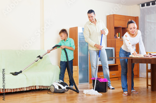 couple with teenage son doing house cleaning
