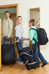 couple and son with luggage near door