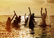 Silhouettes of people jumping in ocean