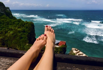 Beautiful women's feet  on background of ocean