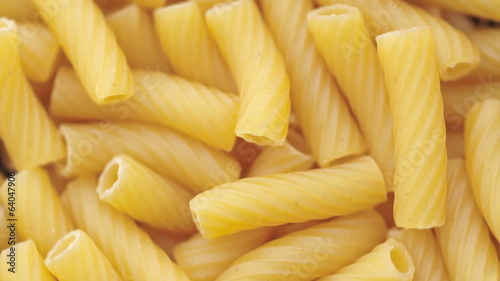Loop able background of uncooked Italian macaroni pasta.