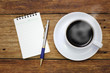 Coffee cup notebook and pen on the wooden table background