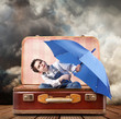 bambino con ombrello seduto in valigia