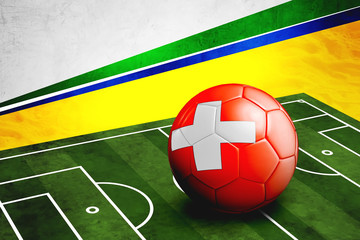Soccer ball with Switzerland flag on pitch