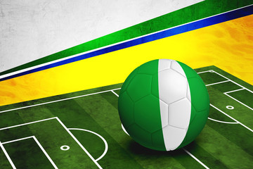 Soccer ball with Nigeria flag on pitch
