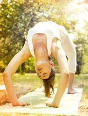 Beautiful young woman doing yoga class in nature.