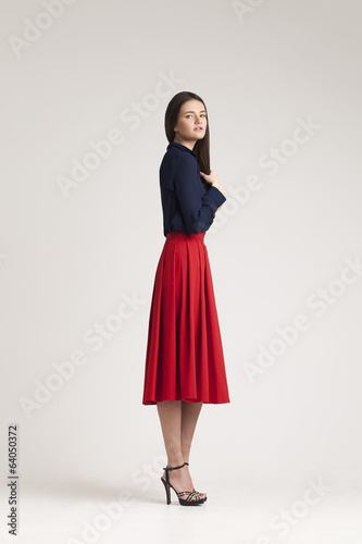 Young  lady in  dress posing on grey background. red