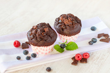 Two delicious homemade chocolate muffins in colored cooking pape
