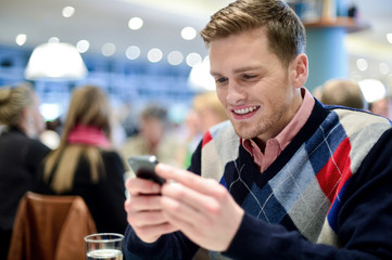 Young man in cafe and using his mobile phone
