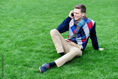 Happy young man using mobile phone on park