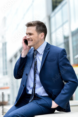 Smiling businessman talking in his mobile phone
