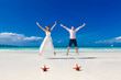 Bride and Groom jumping on tropical beach shore with two red sta