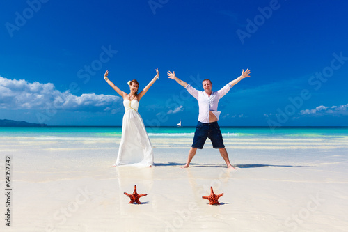 Bride and Groom standing on tropical beach shore with two red st