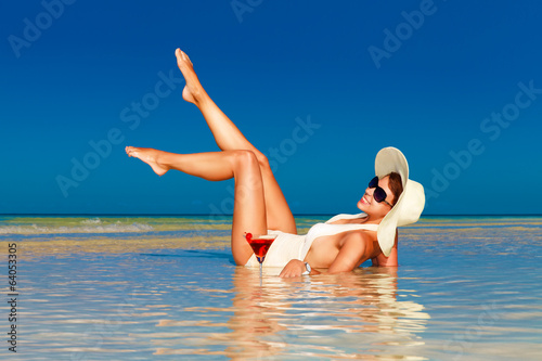 young woman in straw hat laying at the tropical beach and enjoyi