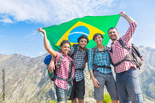 People with Brazilian Flag on top of Mountain