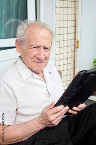 senior man holding a touchpad PC in his hands