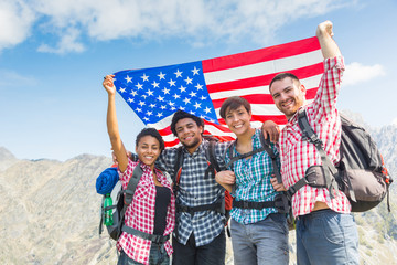 People with USA Flag on top of Mountain