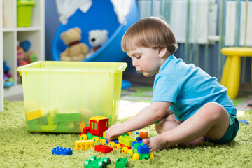kid boy playing with construction set  at home