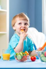 kid boy eating healthy food at home interior