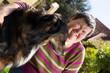 behinderte Frau umarmt einen Hund im Freien