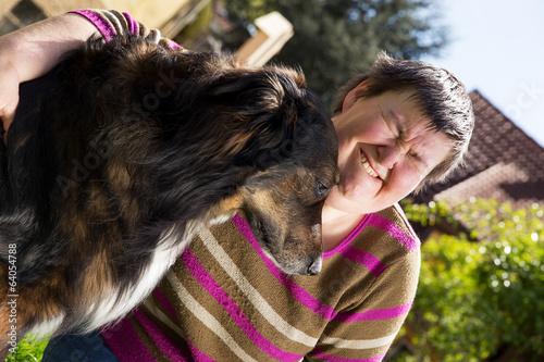 canvas print picture behinderte Frau umarmt einen Hund im Freien