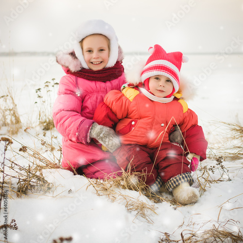 Two beautiful happy sisters in winter outdoors.
