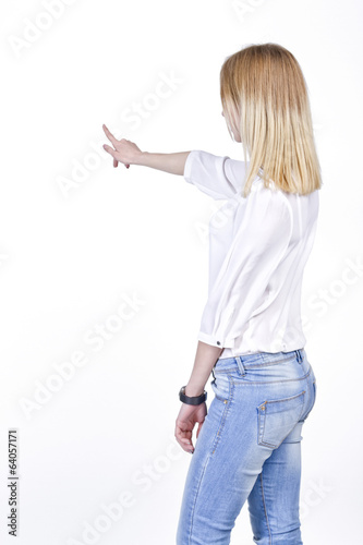 Slender girl in jeans pointing to the virtual object