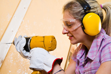 Female carpenter  at work using hand drilling machine